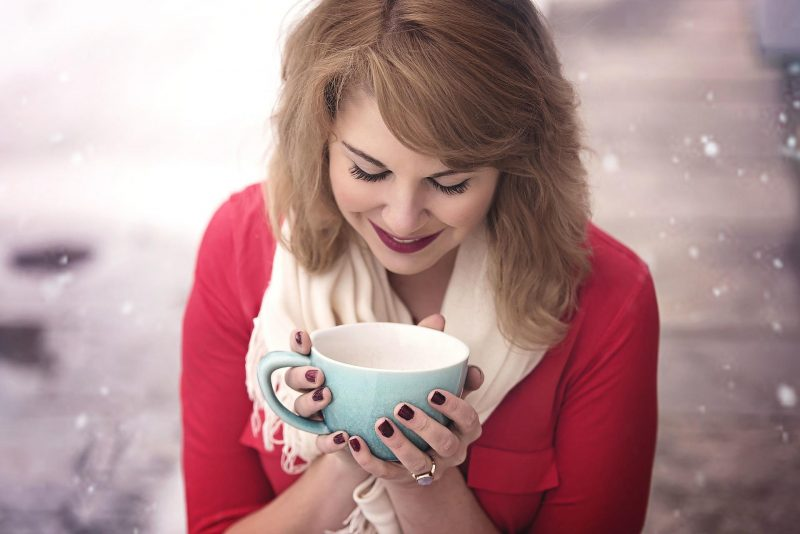 A woman holding a cup in her hands - coffee enthusiasts