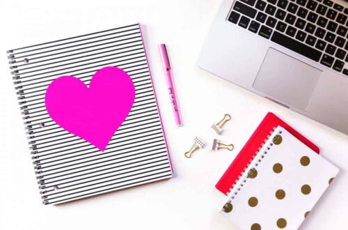 Desk with a notebook with a pink heart on it, a pen, and the edge of a laptop