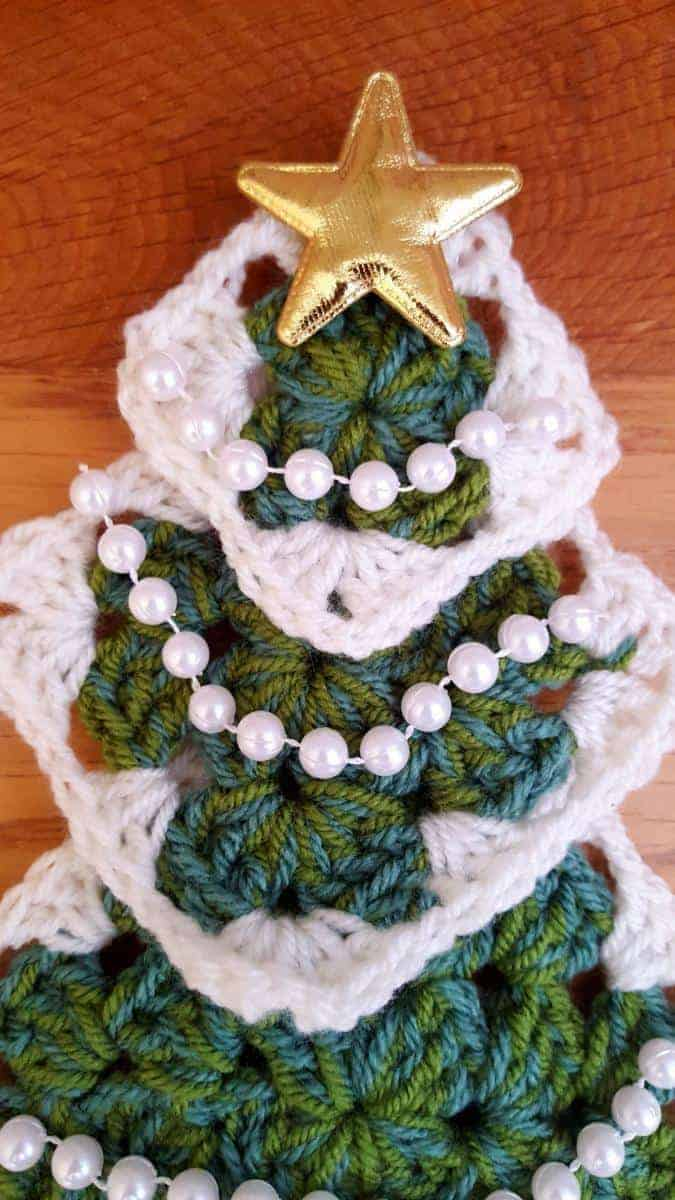 Adding the star to the top of your crocheted Christmas tree wall hanging