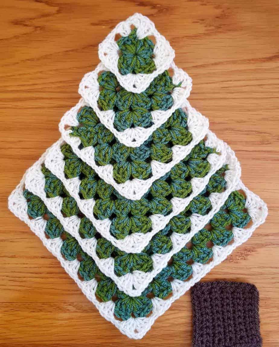 Crochet granny squares laid out to show a Christmas tree and the trunk