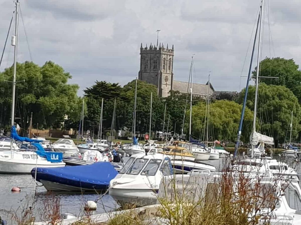 boats on the river stour at Tuckton with Christchurch Priory in the background