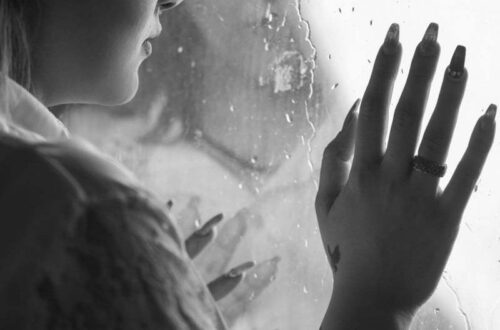 Woman leaning against a window with rain drops