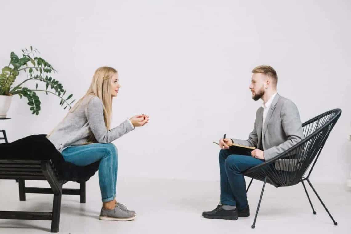 Male therapist and female client sat on chairs talking