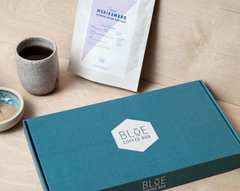 Cup of black coffee, bowl of sugar, coffee sachet, Blue letter box packaging for the coffee subscription from Blue Coffee Box